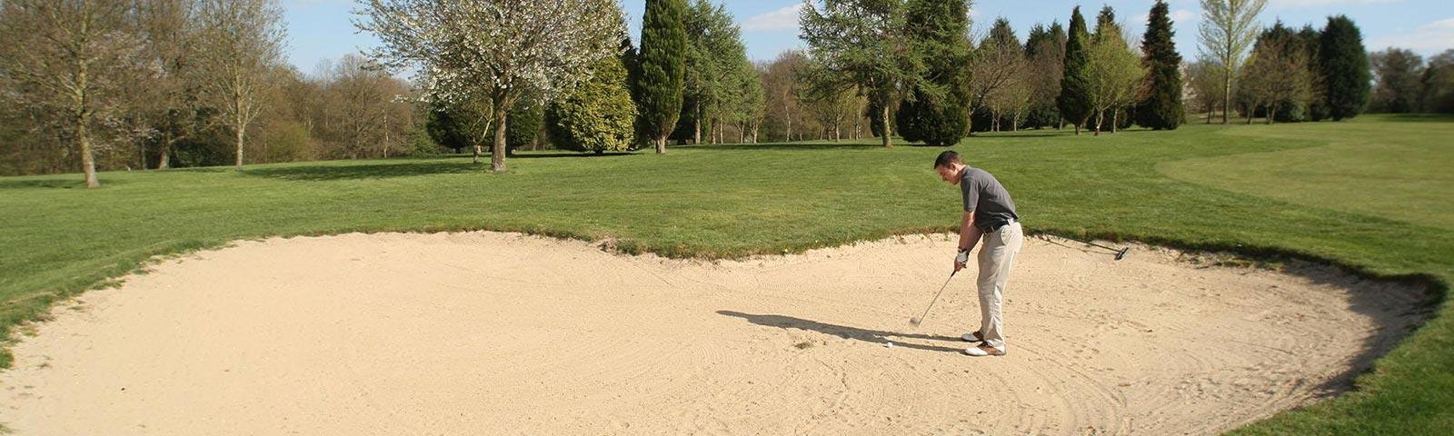 man hitting shot from a sand bunker