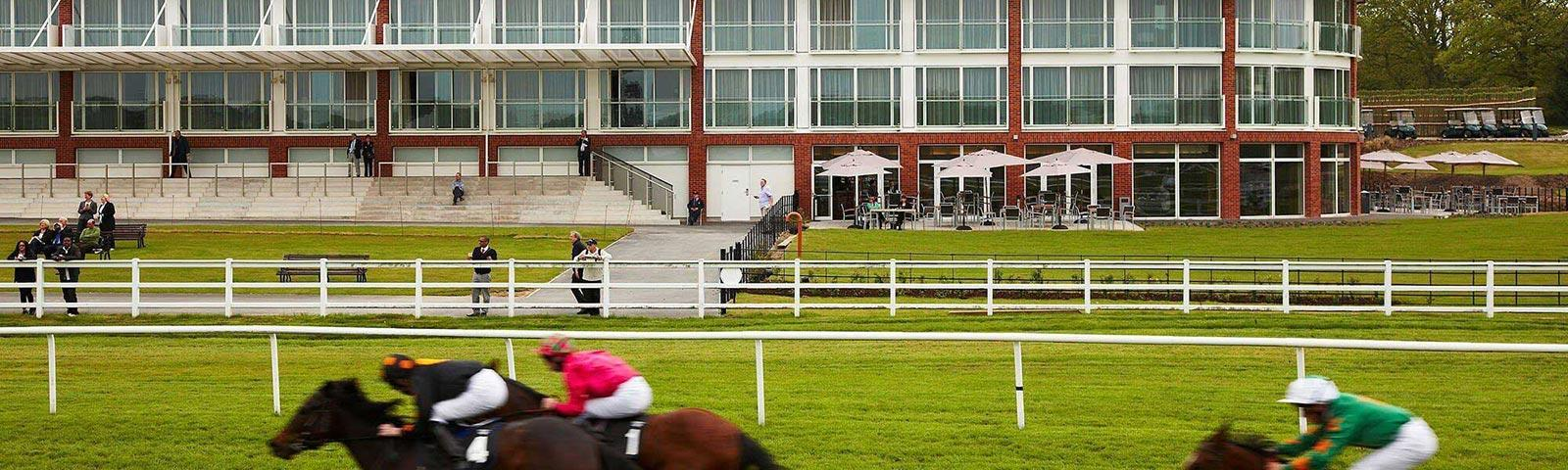 Horses galloping past the main building at Lingfield Park Racecourse.