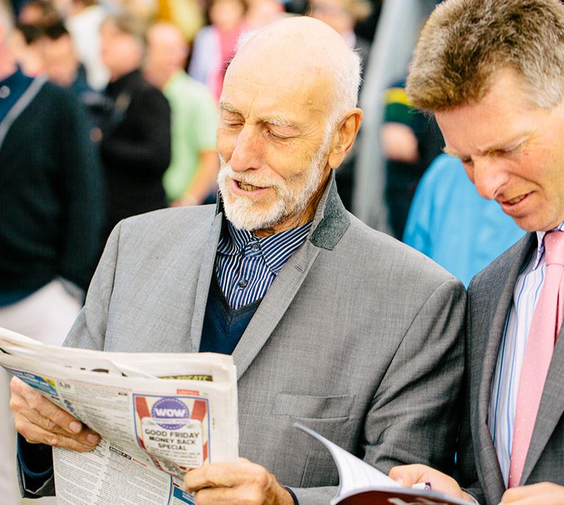 Gentleman reading through a newspaper.