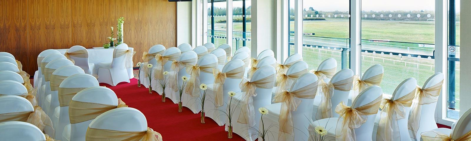 Rows of chairs set up in a room, dressed up for a wedding.